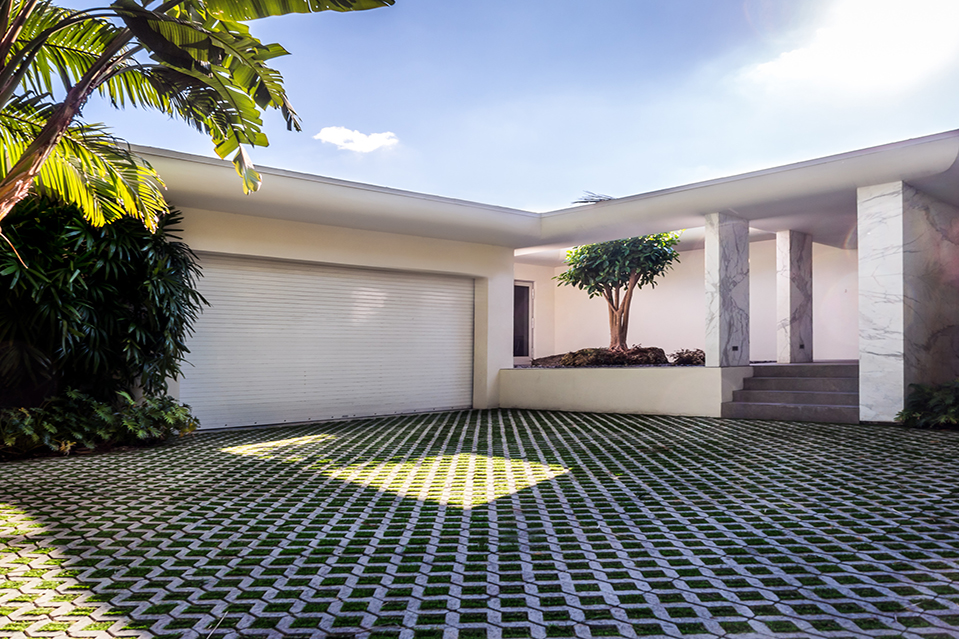 The house sits on a 12,150-square-foot lot. The driveway features hand-placed squares of artificial g
