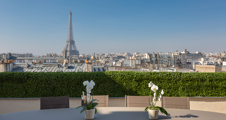 The living room opens to a terrace with Eiffel Tower views.