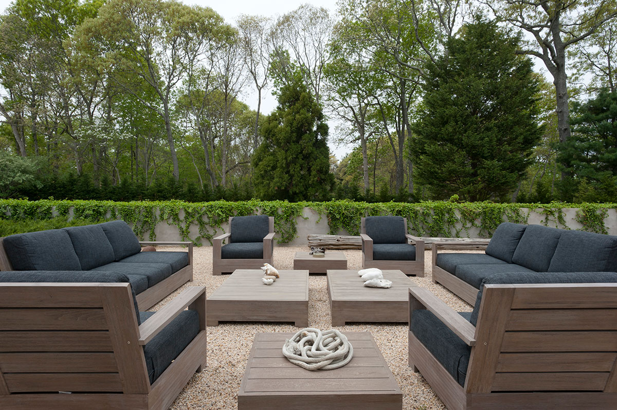 Neutral tones, gravel flooring, and wooden furniture create a Zen-like outdoor living room for this H