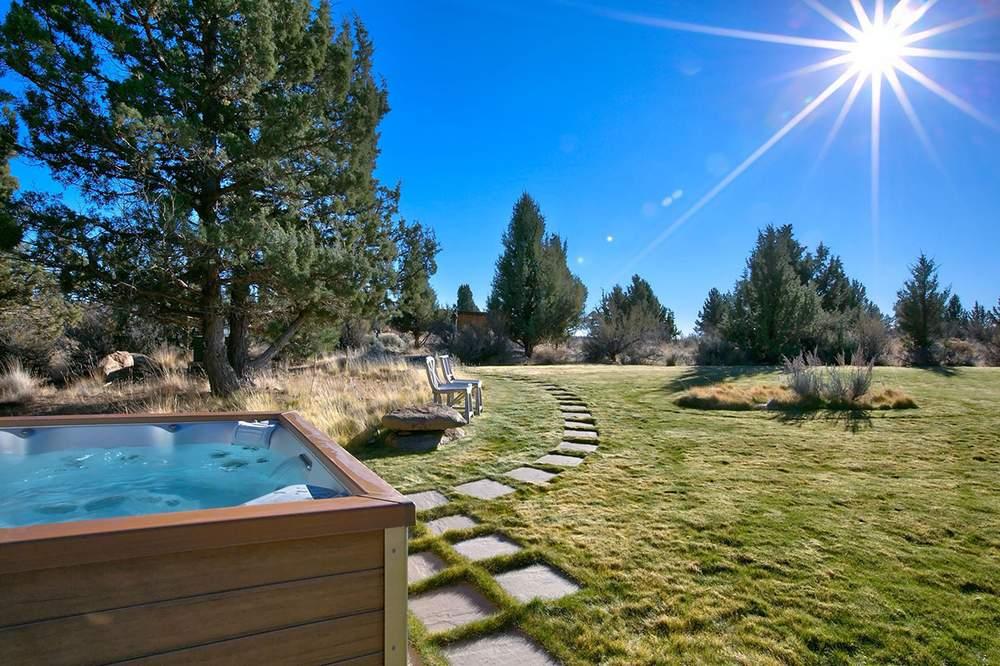铺有草坪的室外空间,以及一个加热浴缸。Cascade Sothebys International Realty
