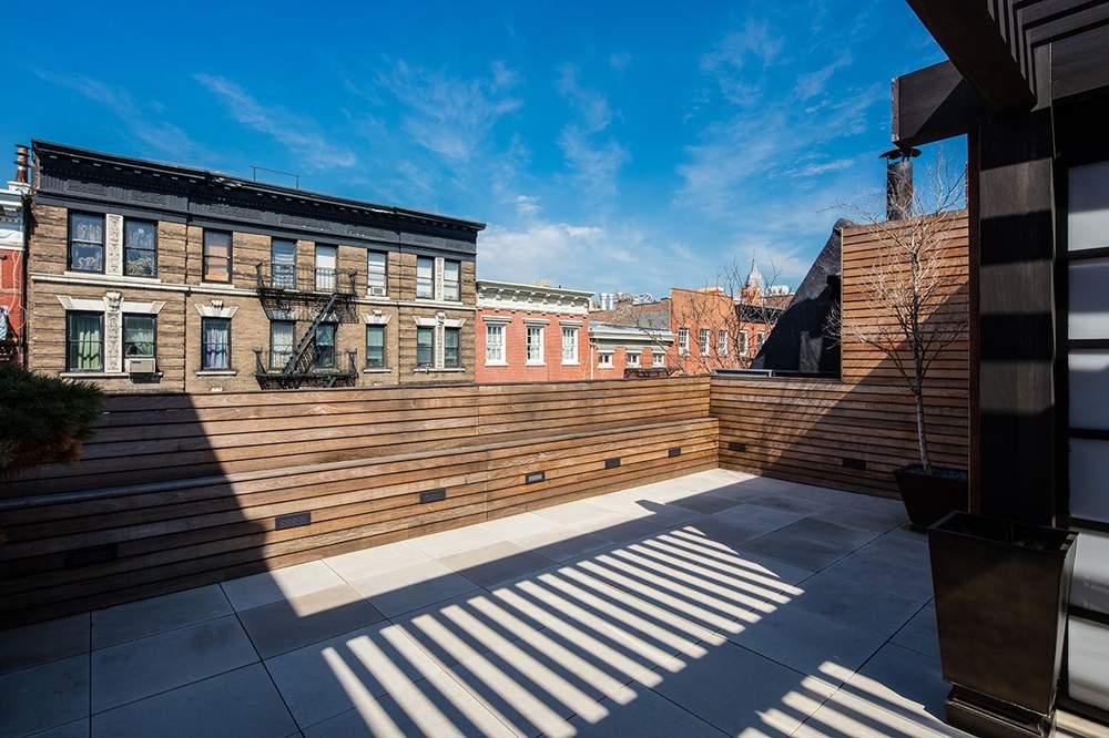 屋顶露台铺有印第安纳石灰石地砖,还建有一个西班牙柏木凉亭。由此向北可眺望帝国大厦,向南可一览世贸中心天际线。(图片来源:Dolly Lenz Real Estate)